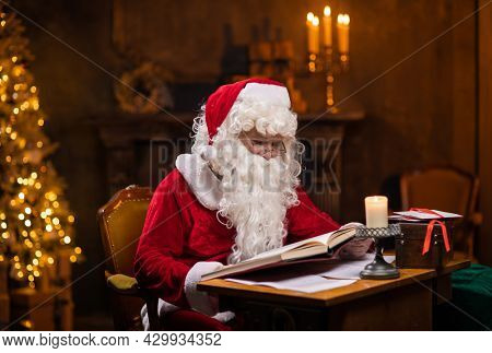 Workplace of Santa Claus. Cheerful Santa is reading the book of wishes while sitting at the table. Fireplace and Christmas Tree in the background. Christmas concept.