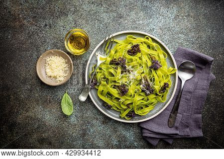 Green Tagliatelle Pasta With Purple Cauliflower On Blue Background, Top View