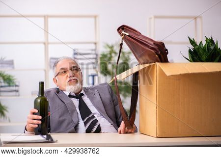 Old alcohol addicted male employee in dismissal concept