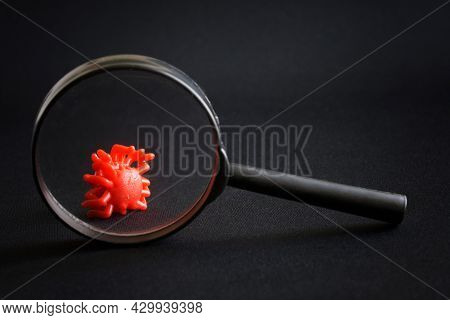 Toy Virus Under A Magnifying Glass Against A Black Background. The Concept Of Studying New Viruses,