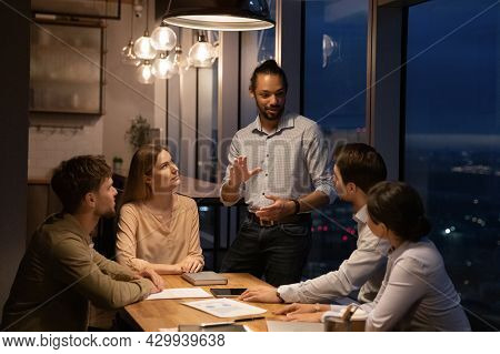 Group Of Diverse Employees Working In Office Boardroom Until Late