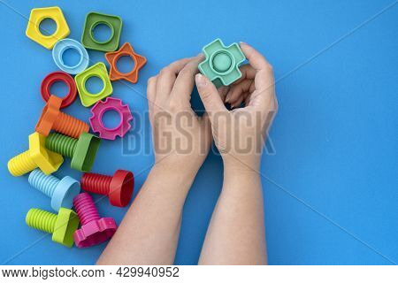 Hands Collect Educational Constructor For Children, Nuts And Bolts In The Form Of Geometric Shapes.
