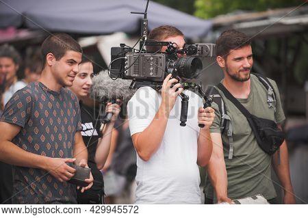 Behind The Scenes. Film Crew Team Shooting Movie Scene On Outdoor Location. Group Filmmaking Set Pro