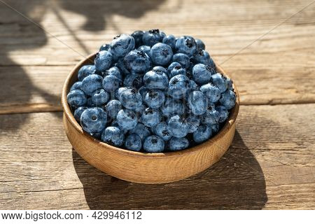 Blueberries In A Round Wooden Plate Close-up. Blueberries On A Wooden Background. Healthy Food. Harv