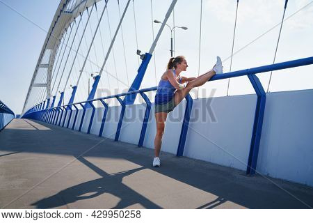 Mid Adult Woman Runner Stretching Outdoors On Bridge In City, Healthy Lifestyle Concept.