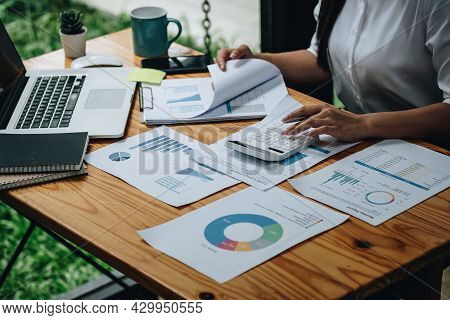 Close Up Woman Calculating Using Machine Managing Household Finances At Home, Focused Biracial Male