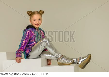 Cute Little Girl Sitting On A White Cube Cross-legged. Concept Happy Childhood, Style And Fashion.