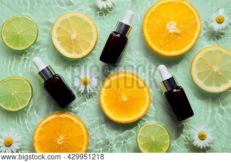 Beauty Background With Organic Cosmetics Products Bottles, Citrus Fruits, Concentric Circles And Rip