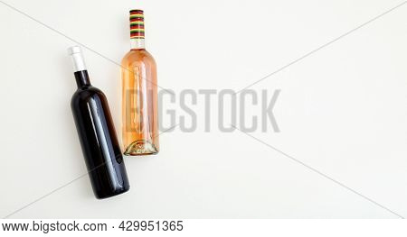 Rose Wine Bottle And Red Wine Bottle . Minimalistic Wine Composition Top View On White Background Co