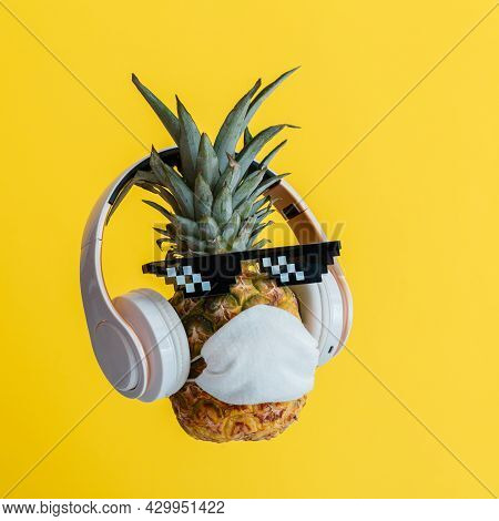 Creative Funny Pineapple Face Wearing Glasses Headphones And Protective Medical Mask. Resting Levita