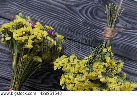 Two Bouquets Of Statice. One Is Yellow, The Other Is Multi-colored. Against The Background Of Pine B