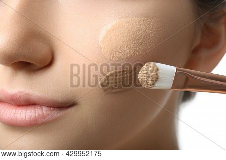 Girl Applying Foundation And Concealer With Brush On White Background, Closeup. Face Contouring