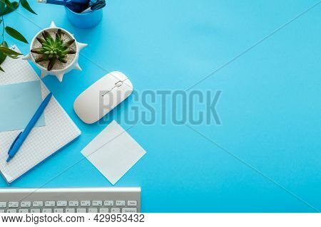 Blue Desk Workspace. Office Table Work Space With Computer Keyboard, Plant Mouse Notepad Stationery