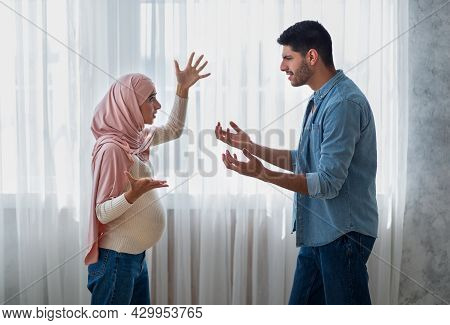 Pregnancy And Relationship Problems. Pregnant Arab Woman Arguing With Husband At Home, Side View