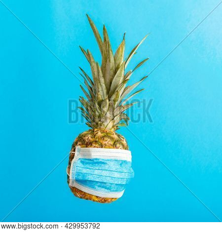 Pineapple In Medical Mask On Color Blue Background. Pineapple Fruit In Face Mask On Summer Backgroun