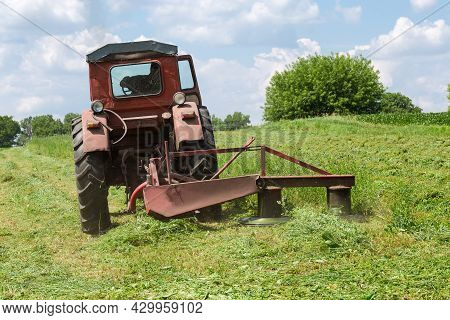 Rotary Mower Mounted On Small Old Tractor During Hay Mowing On A Hayfield At Summer Day