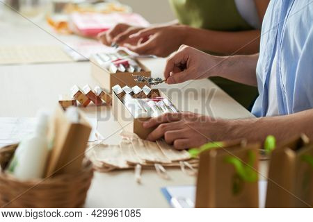 Hands Of People Putting Handmade Soap In Boxes And Decorating With Lavender Branches