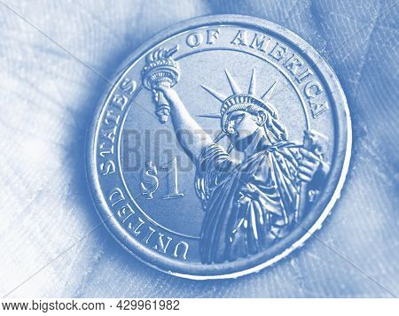 Us Coin Lies On The Palm. 1 One Dollar Coin Close Up. Light Pale Blue Tinted Background Or Wallpaper