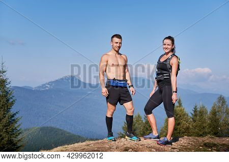 Couple Of Smiling Trail Runners Standing On Top Of Mountain Hill At Bright Sunny Day Against Backgro