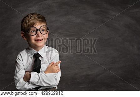 Smiling Little Boy In Glasses Over School Black Board. Funny Happy Child With Crossed Arms Pointing