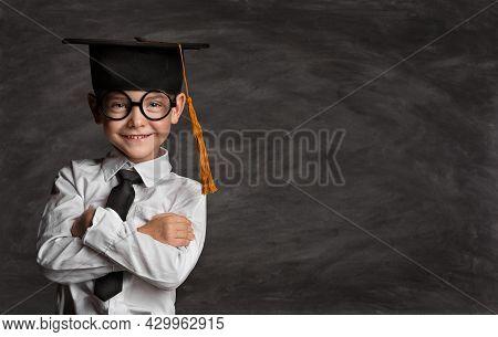 Happy Preschooler Boy In Eyeglasses And Graduation Hat Over Blackboard With Copy Space. Happy Little