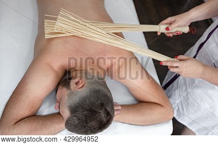 The Masseur Gives A Japanese Massage To A Man With Bamboo Brooms.