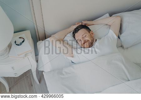 View From Above Of Young Happy Relaxed Caucasian Man With Attractive Smile Sleeping, Lying In Cozy B