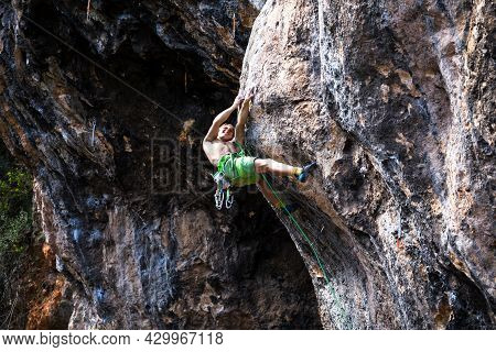 A Young Athlete Climbs A Rock, A Climber Trains On Natural Terrain, A Man Trains Strength And Endura