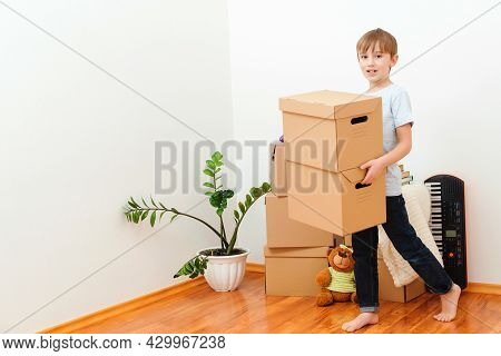 Happy Child Carrying Boxes Into New Home. Moving Day. Happy Boy Having Fun In Moving Day. Housing A