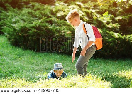 Boy Gives Hand To His Little Brother On A Walk. School Boy Helps To Stand Up His Friend. Children He