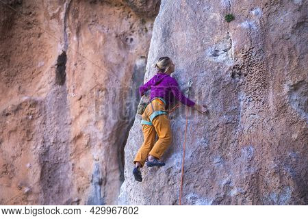 A Girl Trains Strength And Endurance On Rocks, Climbing On Natural Terrain, A Rock Climber Overcomes