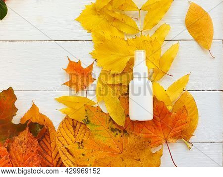 Mockup Of White Plastic Spray Bottle And Bright Autumn Or Fall Leaves On White Wooden Table. Natural