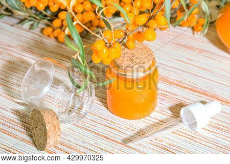 Cosmetological Natural Organic Remedy Oil Tincture Of Orange Sea Buckthorn Berries In A Glass Bottle