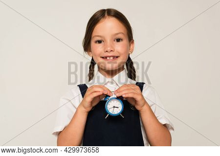 Cheerful Schoolkid Holding Small Alarm Clock While Looking At Camera Isolated On Grey