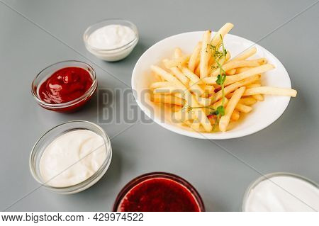 French Fries And Different Sauces Around Plate.