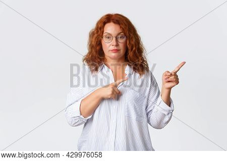 Serious-looking Redhead Middle-aged Woman Telling To Look Right, Stare At Camera Unbothered And Boss