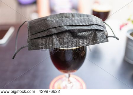 Glass Of Beer, Black Face Mask On A Beer Glass Beer On A Table.coronavirus Restrictions Considering