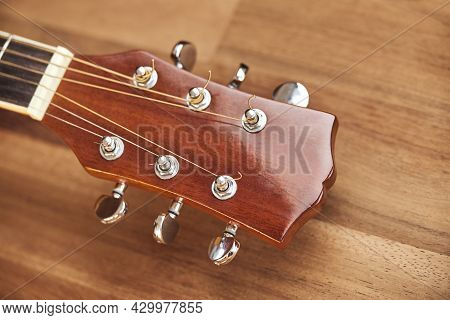 Guitar Headstock On A Wooden Surface. Close-up Horizontal Image.