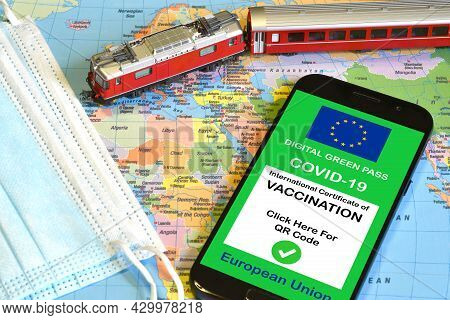 The Digital Green Pass Of The European Union On Smartphone With A Model Red Train And Surgìcal Masks