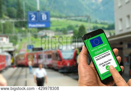 Man In A Train Station Is Holding Smartphone With The European Union Digital Green Pass For Covid-19