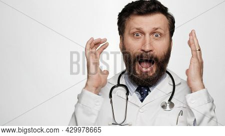 Doctor Is Scared, Terrified. Frightened Man Doctor On White Background Looking At Camera Throws His