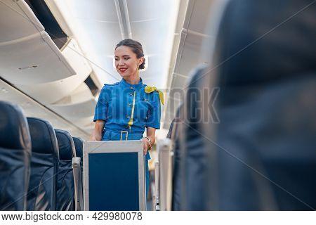 Smiling Female Cabin Attendant Leading Trolley Cart Through Empty Plane Aisle