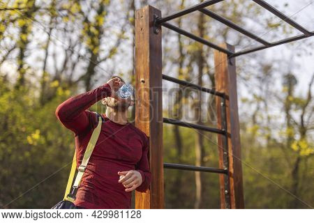 Athletic Young Man Carrying Gym Bag, Drinking Water After An Intense Outdoor Workout In A Street Wor