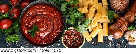 Pasta Background. Pasta Rigatoni, Tomato Ketchup Sauce, Olive Oil, Spices, Parsley, And Fresh Tomato