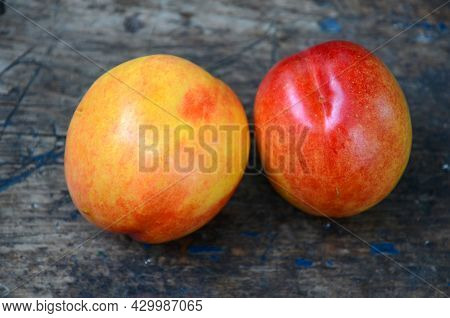 Two Ripe Juicy Fruits Of Nectarine Lie On A Wooden Surface.