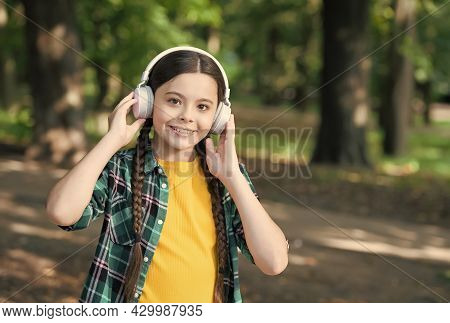 Fine Engineering Only For Your Ears. Happy Kid Wear Ear Phones Natural Outdoors. Little Girl Listen