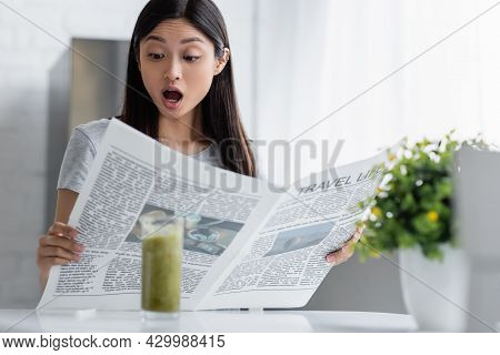 Astonished Asian Woman Reading Travel Life Newspaper Near Blurred Glass With Smoothie.