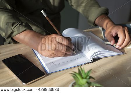 Male Hand Of Planner Writing Daily Appointment On Calendar Book, Working Space At Home. Man Plan And
