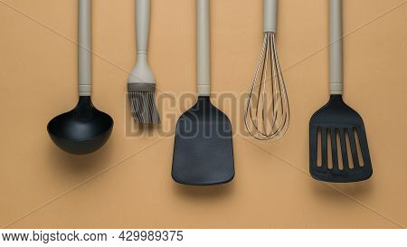 A Set Of Kitchen Tools With Beige Handles On A Light Background. Plastic Kitchen Tools. Flat Lay.