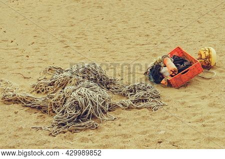 Sandy Beach With Old Fishing Rope Net And Tackle.